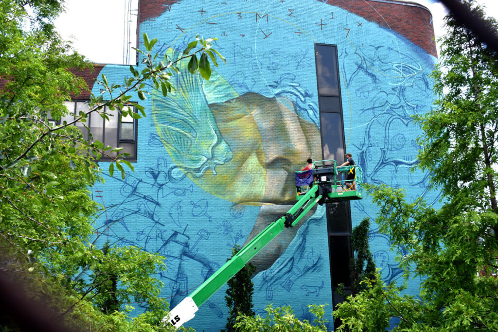 """Beau Stanton of New York paints at the East Boston Fire Station for the """"Sea Walls"""" mural project, July 23, 2021. (©Greg Cook photo)"""