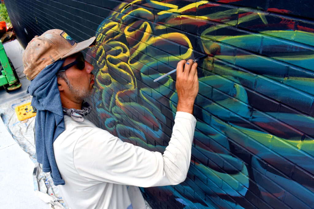 """Felipe Ortiz paints at East Boston Early Education Center for the """"Sea Walls"""" mural project, July 23, 2021. (©Greg Cook photo)"""