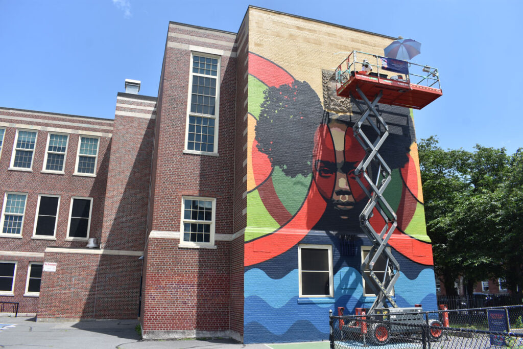 """Nneka Jones of Tampa and Trinidad paints at Donald McKay School in East Boston for the """"Sea Walls"""" mural project, July 23, 2021. (©Greg Cook photo)"""