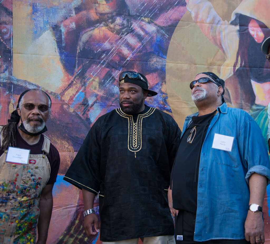 """Paul Goodnight (from left), Rob """"Problak"""" Gibbs and Larry Pierce at the temporary, printed mural """"No Strings Detached"""" at Breeze's Laundromat, Grove Hall, Boston, 2021. (Courtesy Now + There)"""