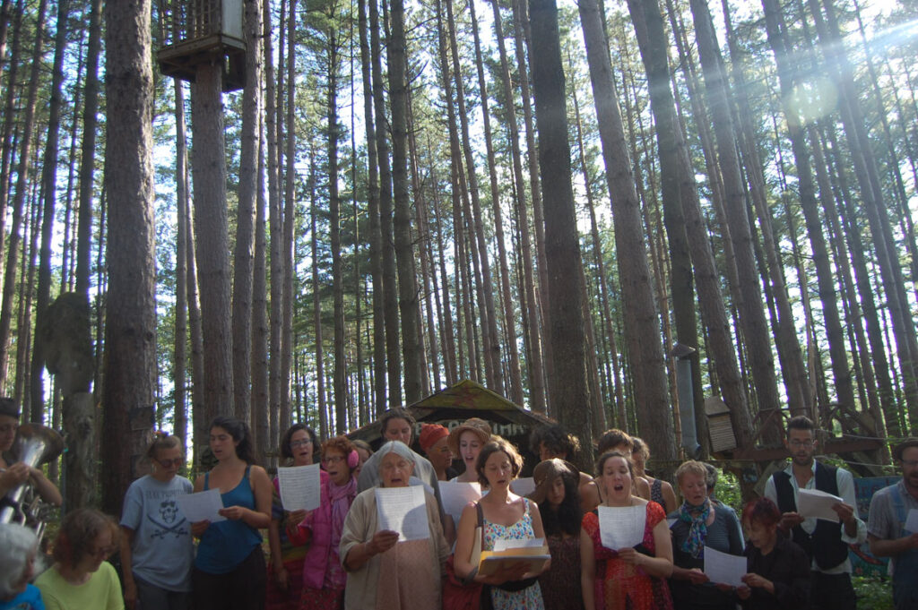 Elka Schumann (center) sings during a memorial in the pine forest at Bread and Puppet, Glover, Vermont, Aug. 21 2015. (©Greg Cook photo)