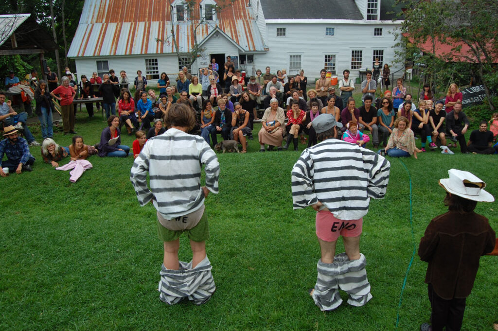 Elka Schumann (seated in front row, center) watches a circus rehearsal at Bread and Puppet, Glover, Vermont, Aug. 21 2015. (©Greg Cook photo)