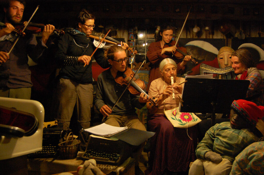 Elka Schumann (seated at center) plays recoder in the Bread and Puppet Museum, Glover, Vermont, Aug. 22 2015. (©Greg Cook photo)