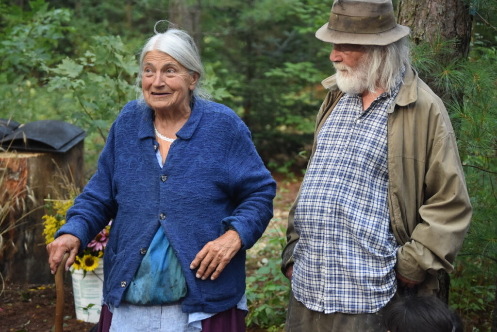 Elka and Peter Schumann in the pine forest at Bread and Puppet, Glover, Vermont, Aug. 18, 2018. (©Greg Cook photo)