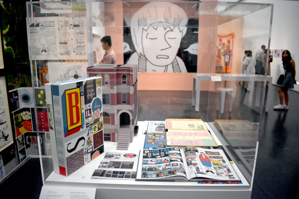 """Chris Ware's """"Building Stories"""" comics in foreground with enlarged John Porcellino panel in background. In """"Chicago Comics"""" at Chicago's Museum of Contemporary Art, July 3, 2021. (©Greg Cook photo)"""