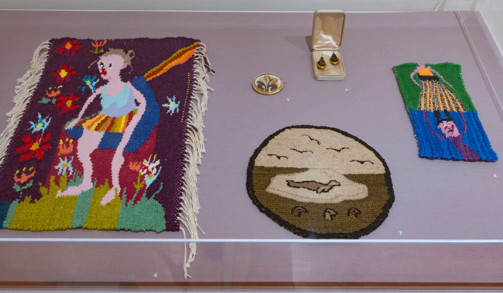 """Christina Forrer artworks at left and right with broaches and polar bear table mat in between, at """"Christina Forrer / MATRIX 187"""" at Wadsworth Atheneum Museum of Art, 2021. (Courtesy Wadsworth Atheneum Museum of Art)"""