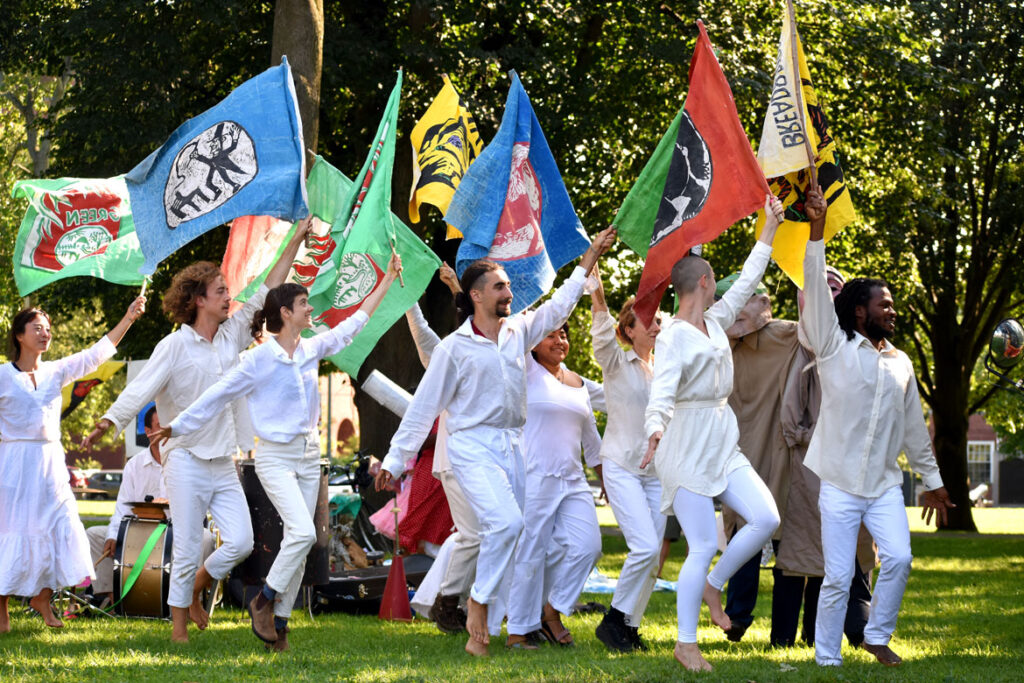 """Flag act opens Bread and Puppet Theater's """"Circus"""" at Cambridge Common, Sept. 4, 2021. (©Greg Cook photo)"""