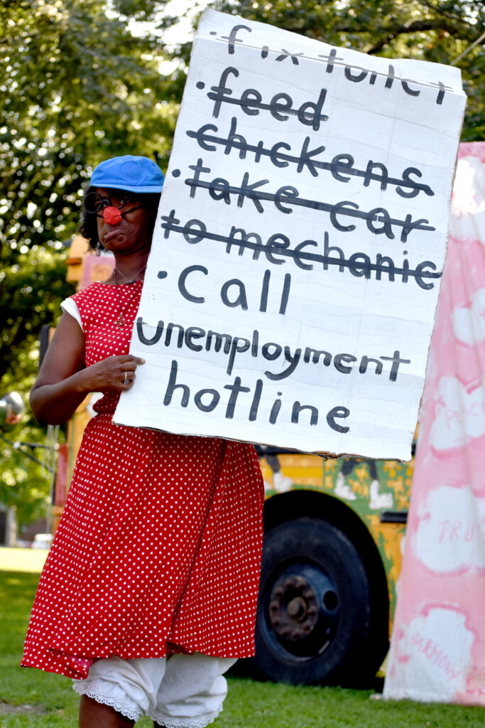 """Struggling to get through to the unemployment hotline in Bread and Puppet Theater's """"Circus"""" at Cambridge Common, Sept. 4, 2021. (©Greg Cook photo)"""