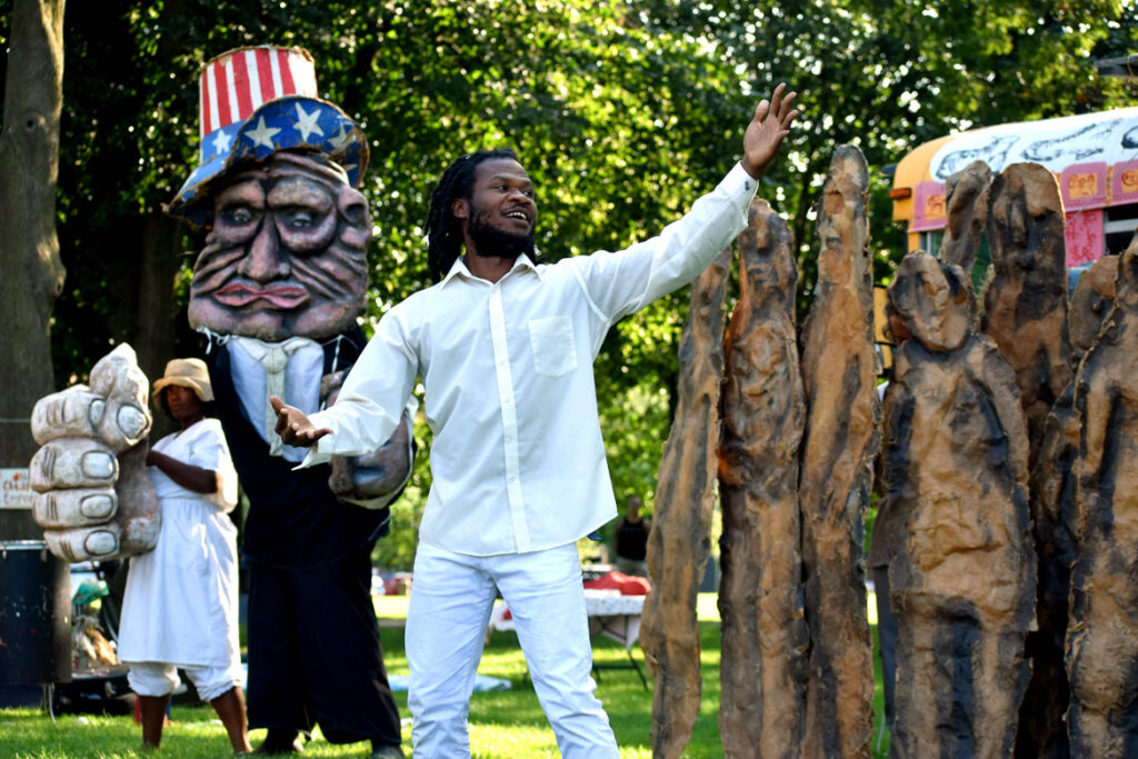 """U.S. manipulations of Haiti in Bread and Puppet Theater's """"Circus"""" at Cambridge Common, Sept. 4, 2021. (©Greg Cook photo)"""