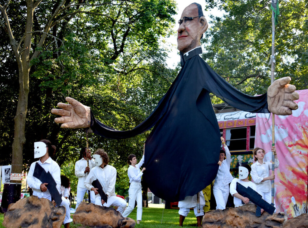 """Remembering the 1980 murder of Archbishop Oscar Romero in El Salvador during Bread and Puppet Theater's """"Circus"""" at Cambridge Common, Sept. 4, 2021. (©Greg Cook photo)"""