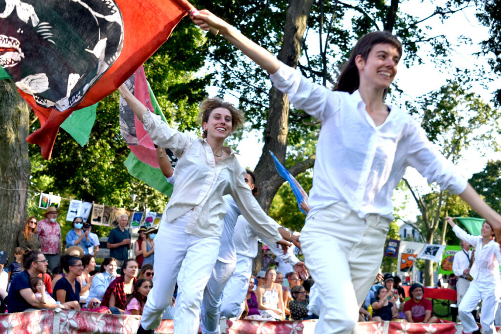 """Flags at the end of Bread and Puppet Theater's """"Circus"""" performed at Cambridge Common, Sept. 4, 2021. (©Greg Cook photo)"""