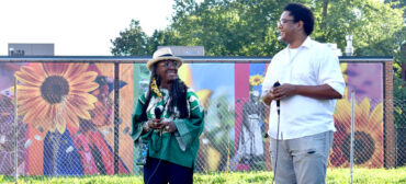 """Ekua Holmes (left) and London Parker-McWhorter talk about there temporary, printed murals """"Honoring the past, seeding the future,"""" at Breeze's Laundromat at 345 Blue Hill Ave., Boston, Sept. 8, 2021. (©Greg Cook Photo)"""