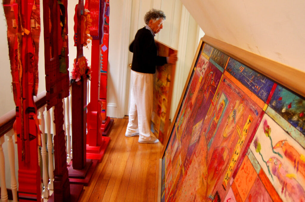Norman LaLiberté moving a painting among the artworks store in the upper floor of his Nahant home, Sept. 4, 2015. (©Greg Cook photo)
